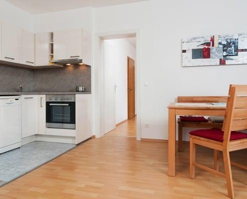 Apartment Karawankenblick Küche und Esstisch. Durchgang Richtung Schlafzimmer mit Doppelbett