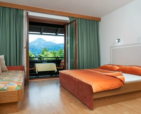 Schlafzimmer mit Doppelbett im Apartment Karawankenblick. Zusatzbett und Balkonzugang.