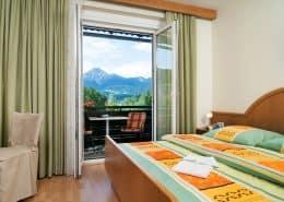 Schlafzimmer mit Doppelbett im Apartment Berg und Seenwelt. Balkonzugang mit Sitzmöglichkeit und Ausblick auf Faaker See und Karawanken.