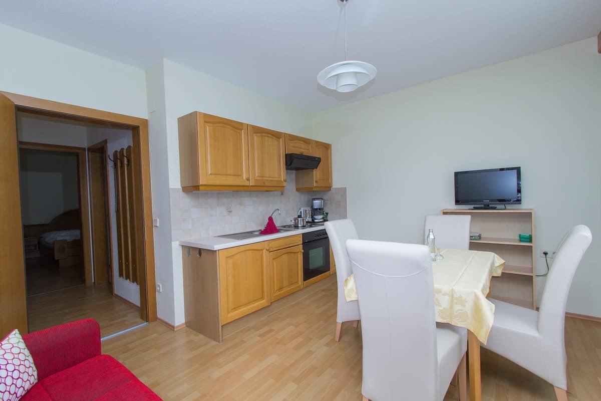 Küchenbereich mit Sitzmöglichkeit im Apartment Morgensonne mit Durchgang zum Schlafzimmer